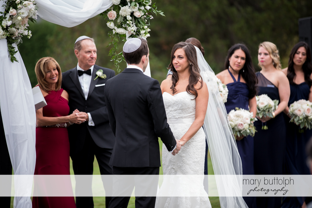 Couple hold hands as they face each other during the wedding ceremony at the Brewster Inn Wedding