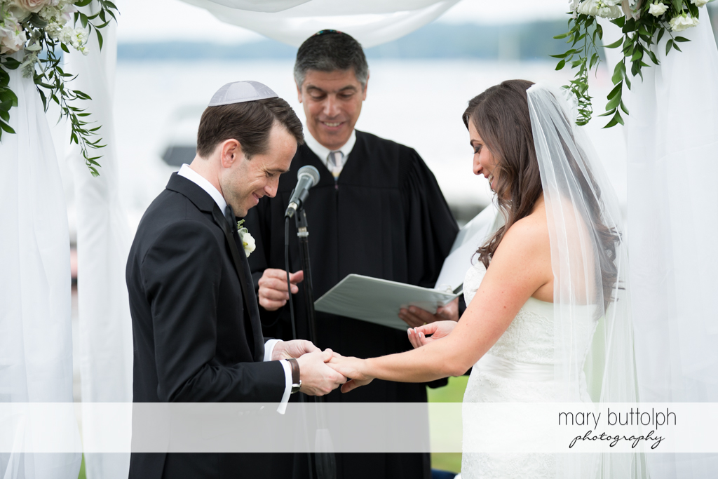 Groom slips the wedding ring on the bride's finger as the priest looks on at the Brewster Inn Wedding