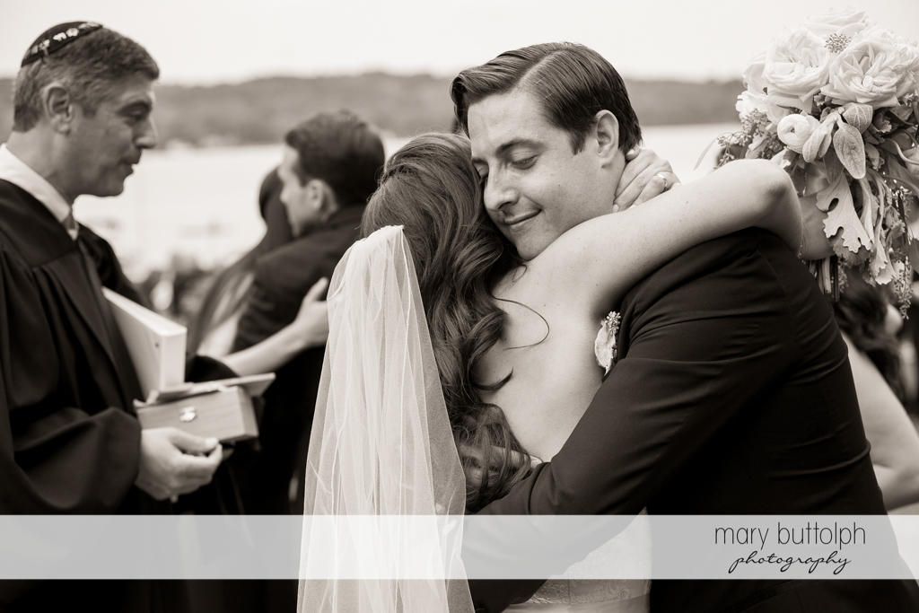 Bride embraces a guest after the wedding ceremony at the Brewster Inn Wedding