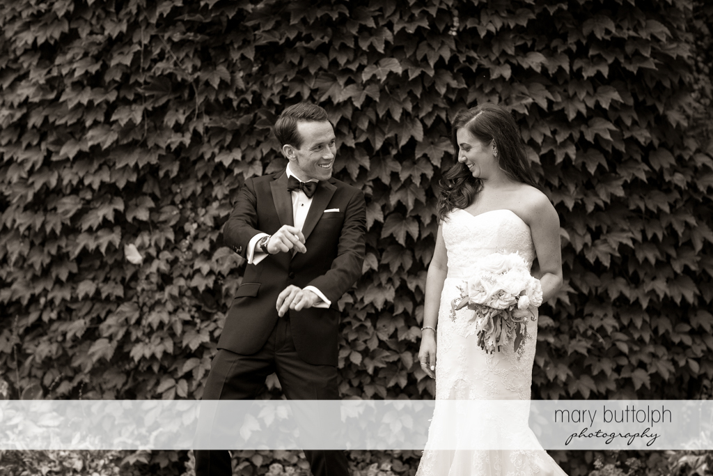 Groom strikes a pose as the bride watches him in the garden at the Brewster Inn Wedding
