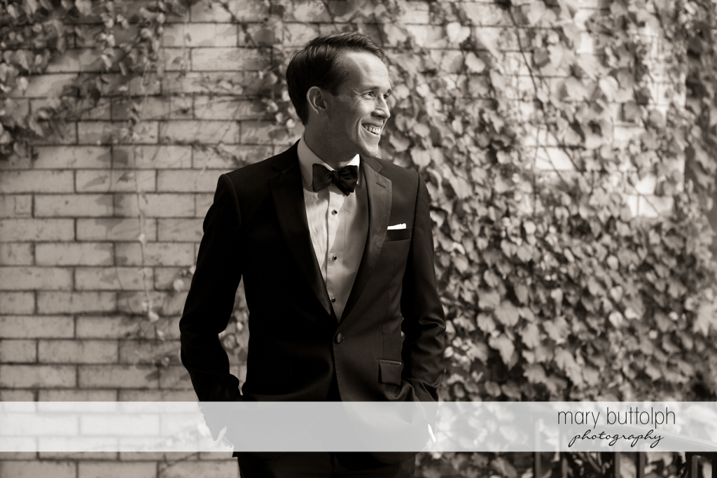 Groom stands in front of a brick wall in the garden at the Brewster Inn Wedding