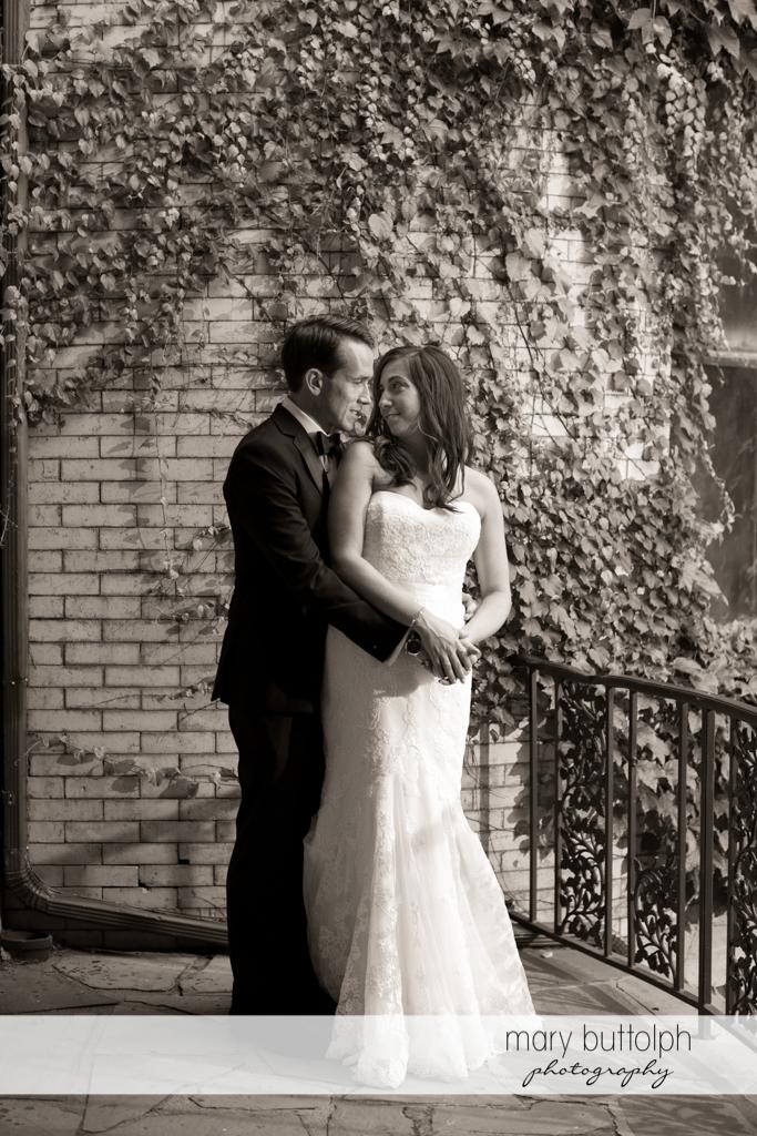Couple stand near a brick wall at the Brewster Inn Wedding