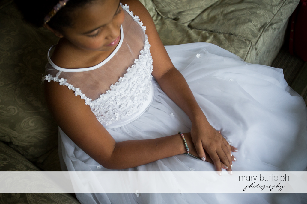 Flower girl sits patiently on the couch at the Brewster Inn Wedding