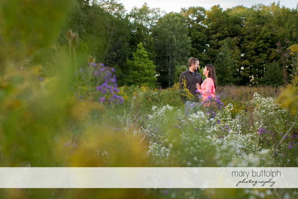 Couple in front of flowers in the park at Marcellus Engagement