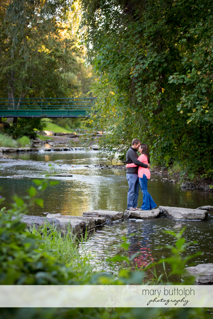 Couple embrace by the lake at Marcellus Engagement