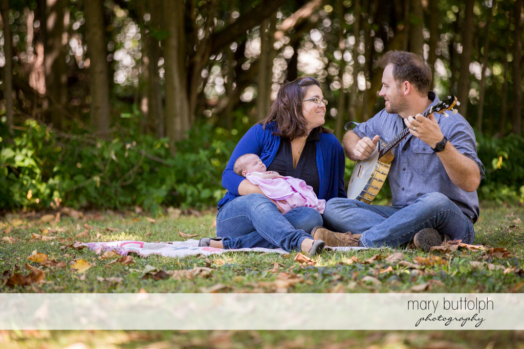 Man plays the banjo for his wife and baby in the garden at Skaneateles Newborn