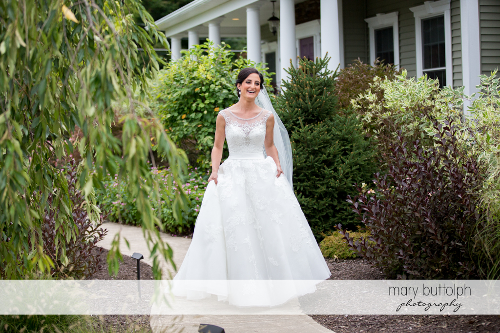 Bride is surrounded by plants in the garden at Anyela's Vineyards Wedding