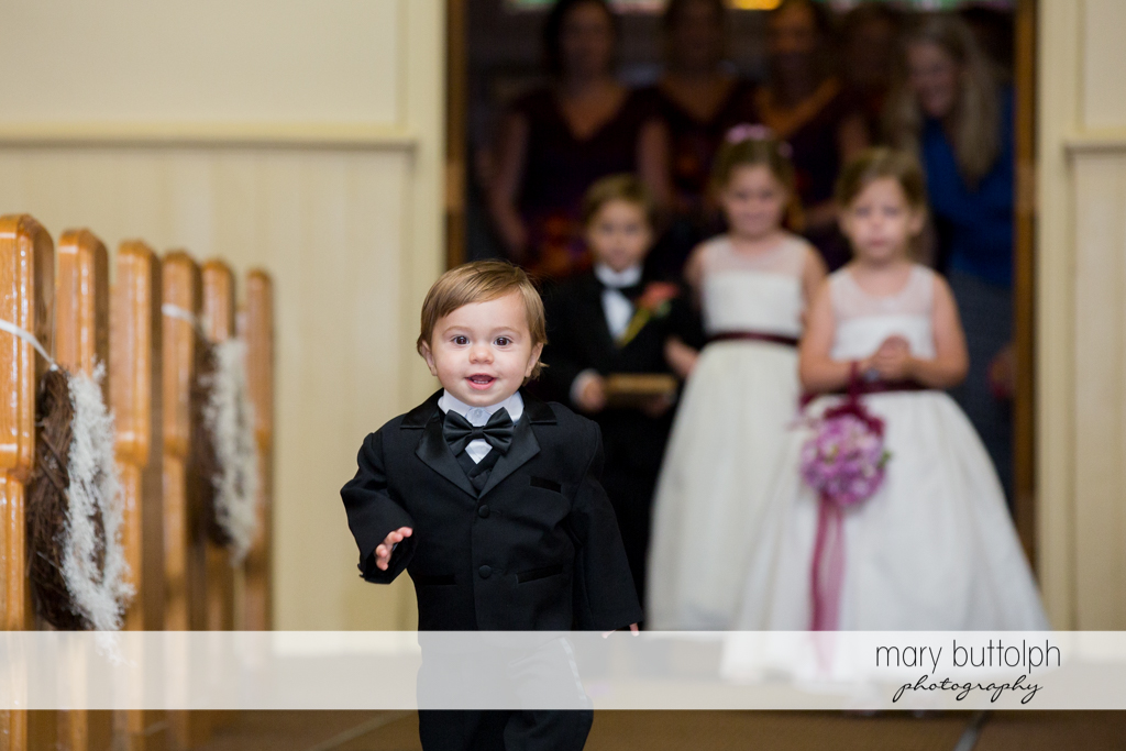 A young member of the wedding party walks down the aisle at Anyela's Vineyards Wedding