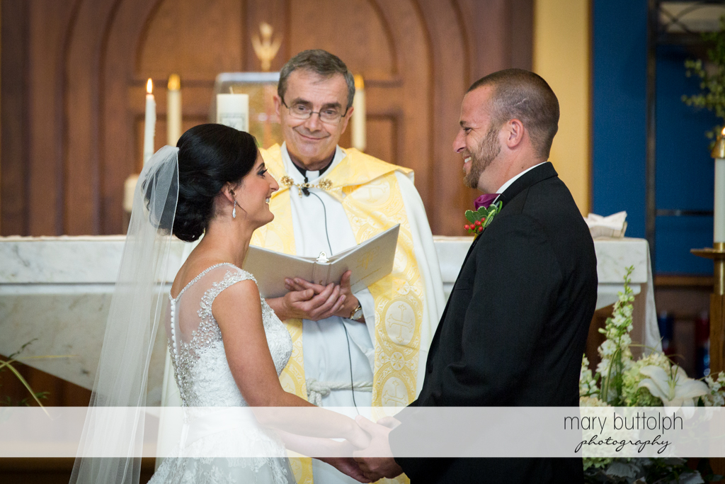 Couple face each each other as the priest looks on at Anyela's Vineyards Wedding