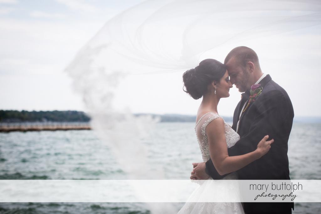 Couple rub noses by the lake at Anyela's Vineyards Wedding