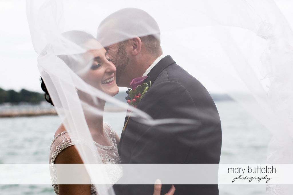Couple as seen through the bride's veil by the lake at Anyela's Vineyards Wedding