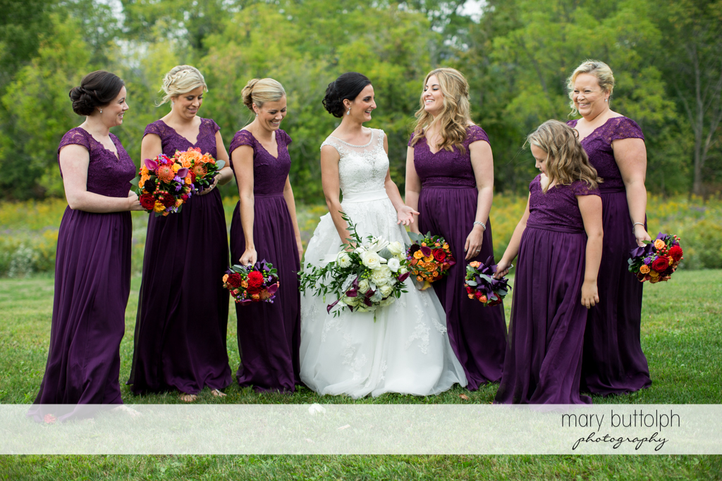 The bride and her bridesmaids with bouquets in the garden at Anyela's Vineyards Wedding