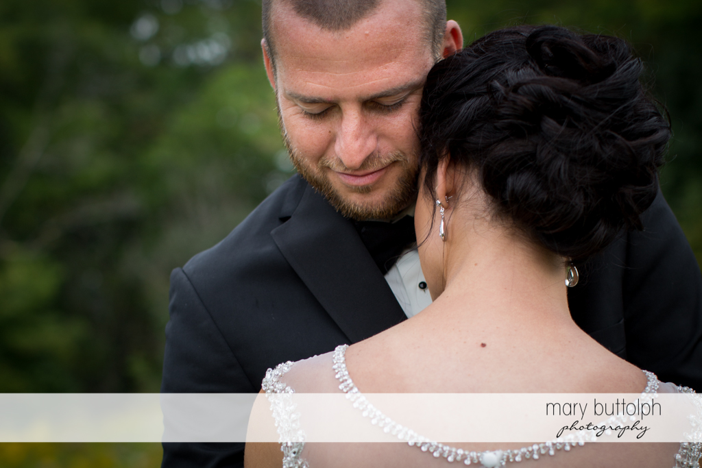 Couple share a tender moment in the garden at Anyela's Vineyards Wedding