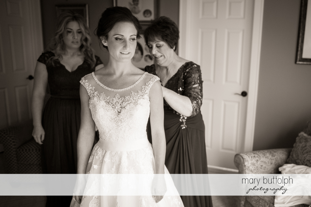 Guests apply the finishing touches to the bride's wedding dress at Anyela's Vineyards Wedding