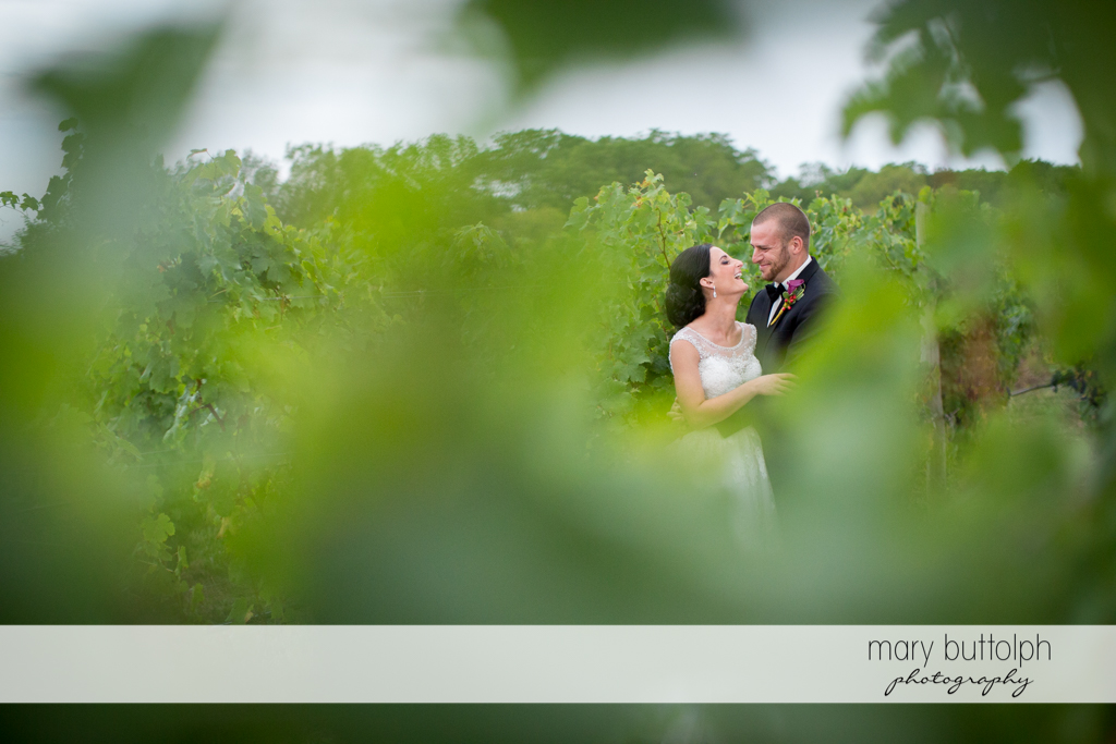 Couple as seen through the leaves of grapevines at Anyela's Vineyards Wedding