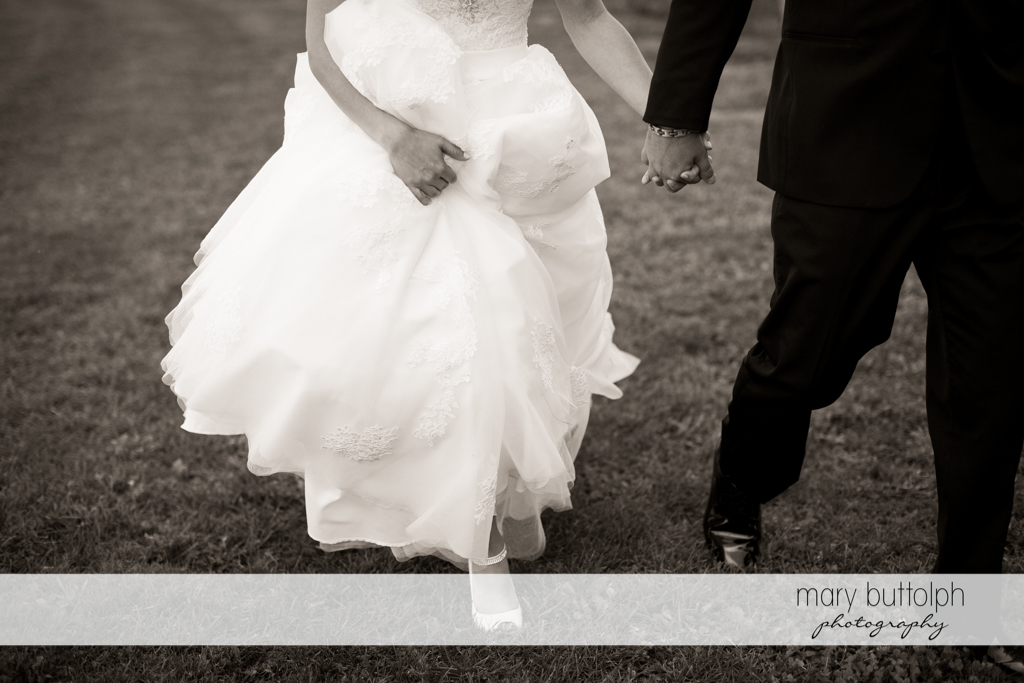 Couple hold hands as they stroll in the garden at Anyela's Vineyards Wedding