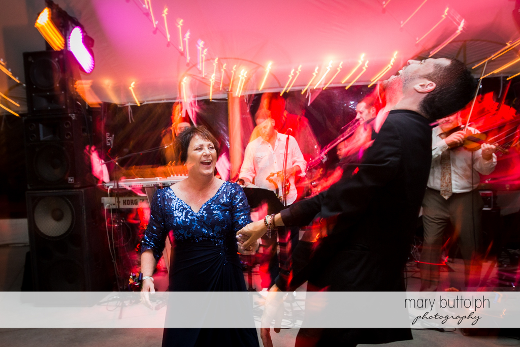 Guests dance beneath the colorful lights at the wedding reception at Anyela's Vineyards Wedding