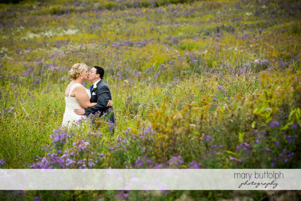 Couple kiss in the meadow at the Lodge at Welch Allyn Wedding