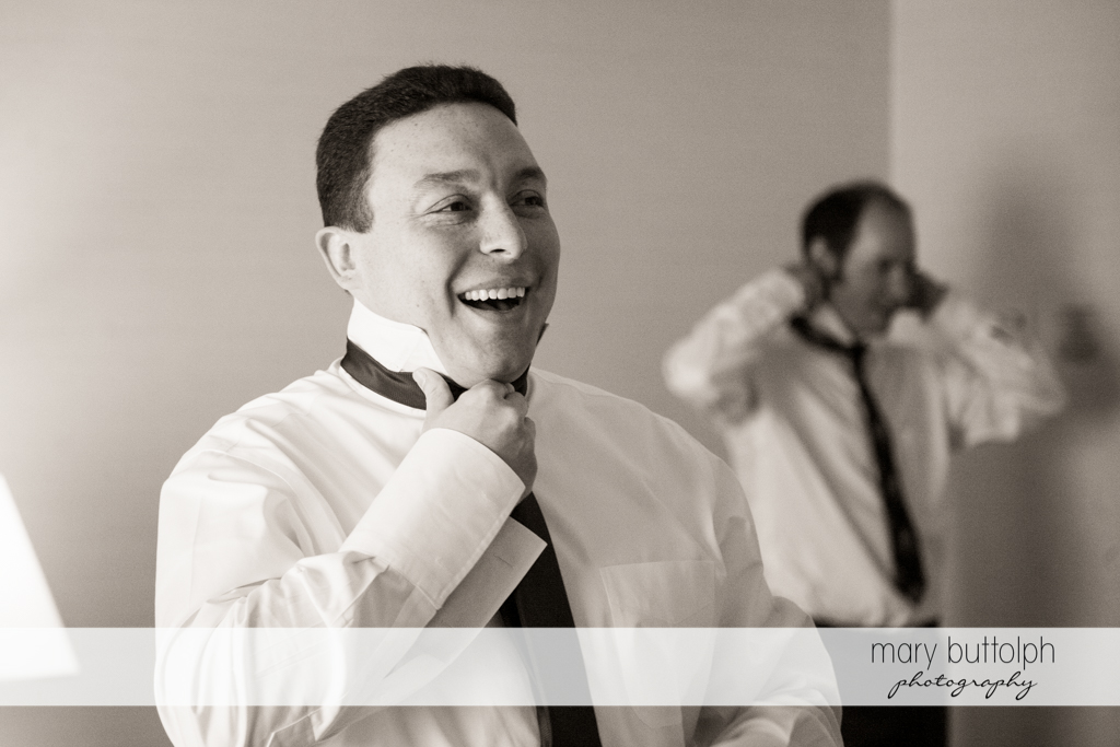 Groom and friend fix their ties at the Lodge at Welch Allyn Wedding