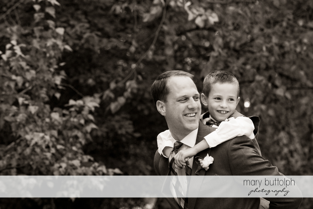 Boy gets a piggyback ride from one of the groomsmen at the Lodge at Welch Allyn Wedding