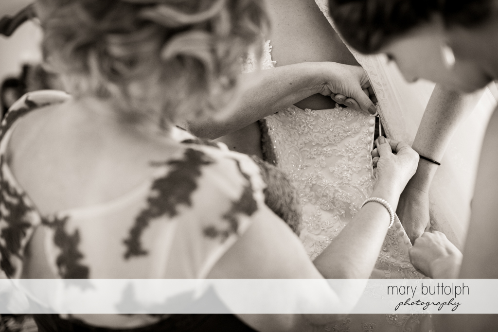 Bride's wedding dress is adjusted by friends at the Lodge at Welch Allyn Wedding