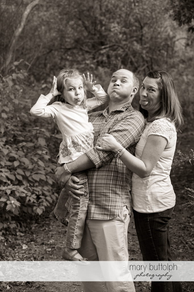 Couple and their daughter make funny faces in the park at Skaneateles Engagement