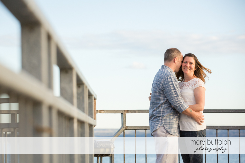 Couple embrace by the lake at Skaneateles Engagement