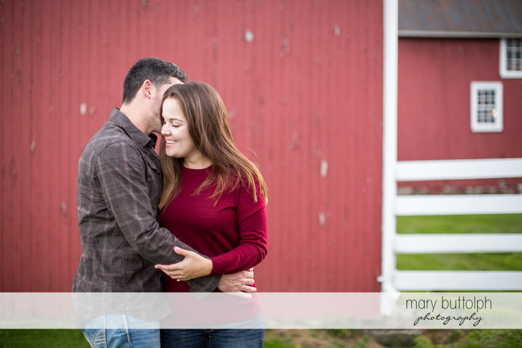 Couple embrace in front of a barn at Geneva Engagement