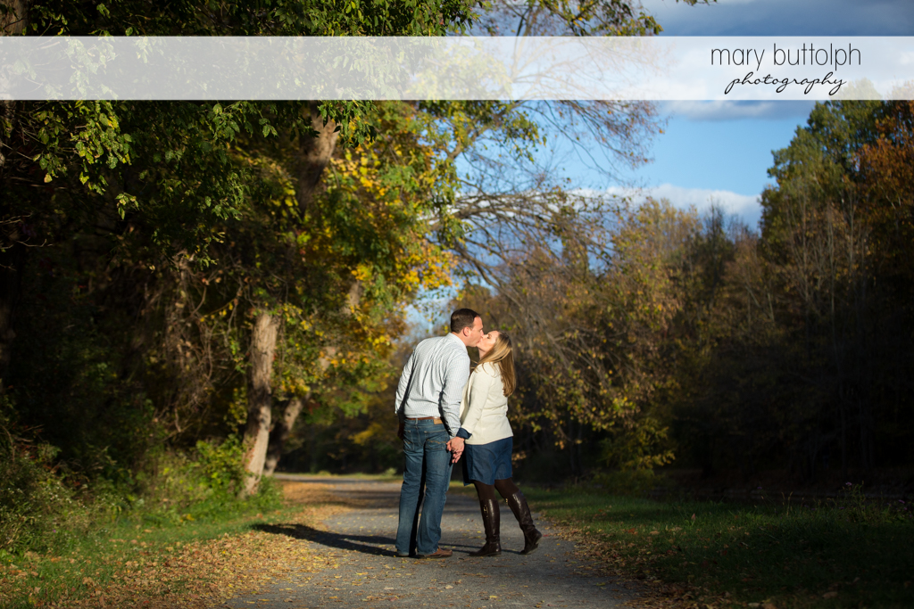 Couple kiss on a wooded trail at Erie Canal Engagement