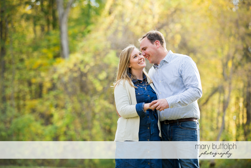 Couple hug on a wooded trail at Erie Canal Engagement