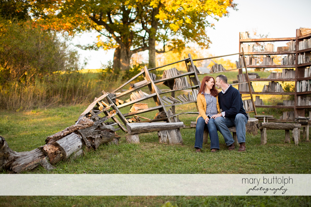Couple sit in front of natural bookshelves in the park at Cazenovia Engagement