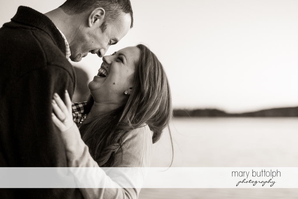 Couple laugh at each other by the lake at Cazenovia Engagement