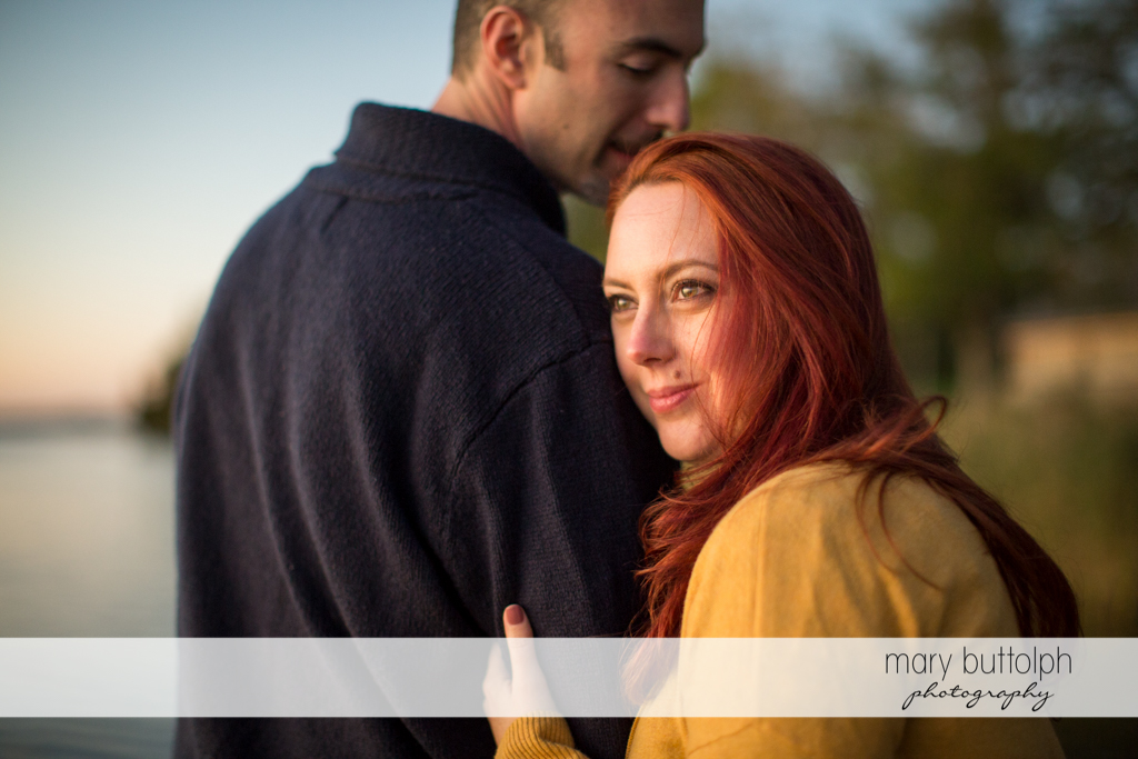 Couple pose by the lake at Cazenovia Engagement