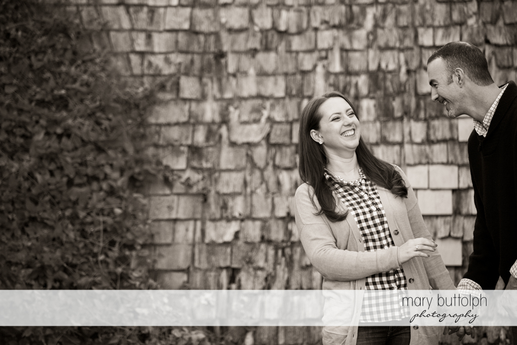Couple share a light moment in front of a brick wall at Cazenovia Engagement