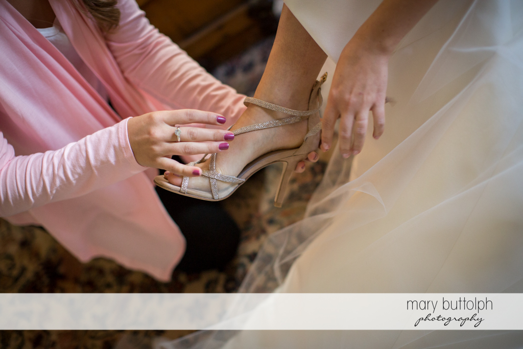 Bride puts on her wedding shoe with a friend's help at Frog Pond Bed & Breakfast Wedding