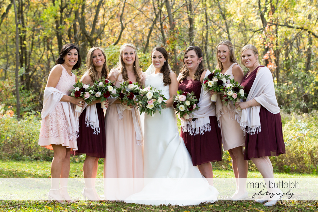 Bride and her bridesmaids with bouquets are photographed together at the Frog Pond Bed & Breakfast Wedding