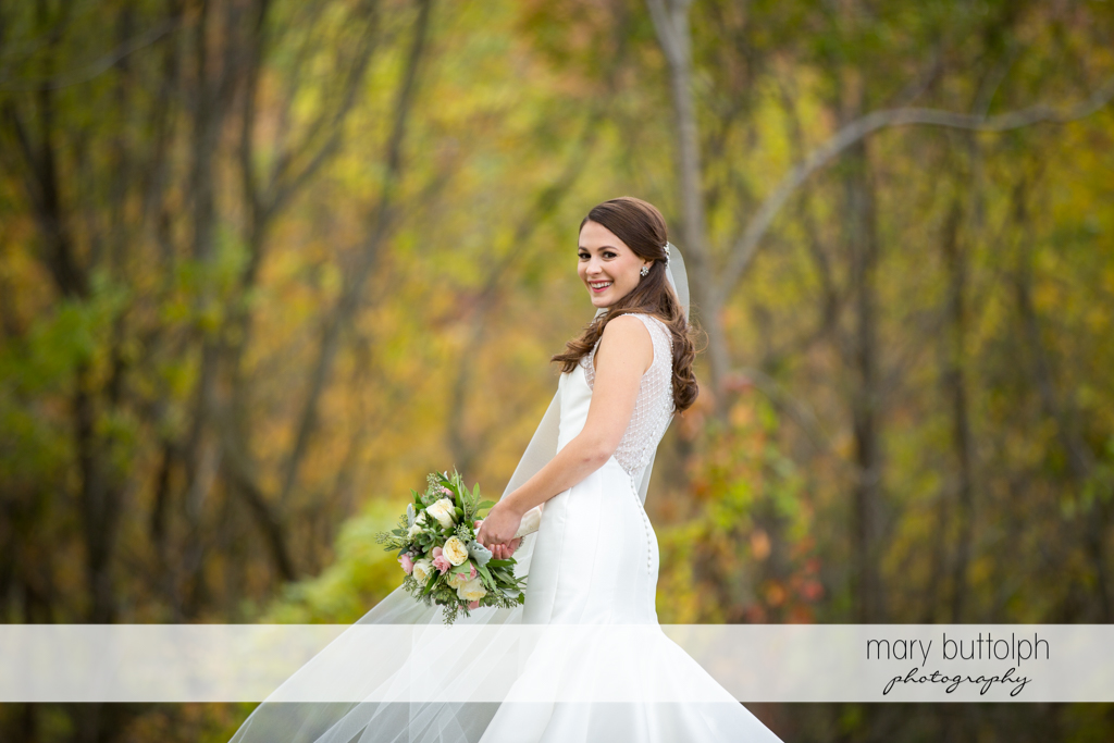 Bride with bouquet looks gorgeous in the woods at the Frog Pond Bed & Breakfast Wedding