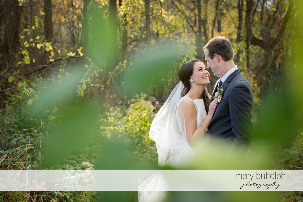 Couple as seen through the leaves in the woods at the Frog Pond Bed & Breakfast Wedding