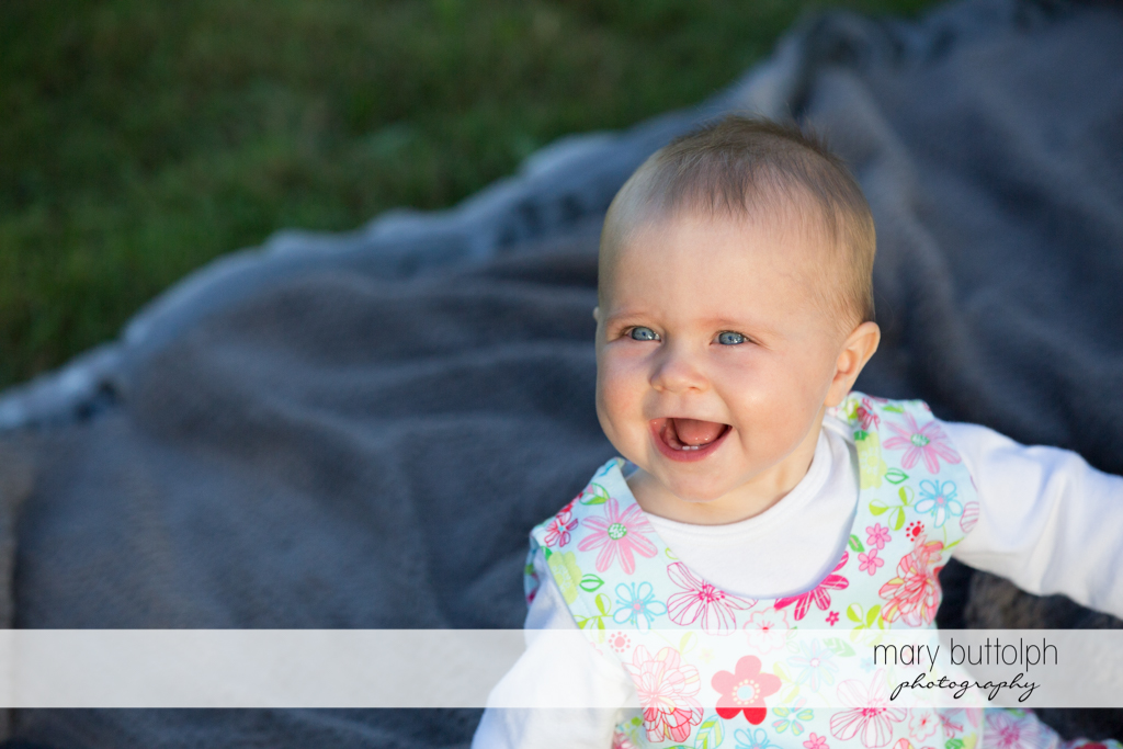 Baby girl flashes her winning smile in the garden at Skaneateles Lake