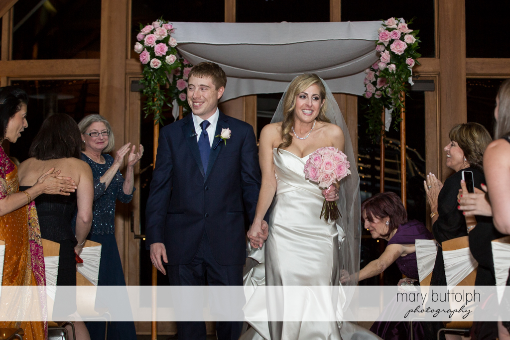 Couple leave after the wedding ceremony as guests look on at the Lodge at Welch Allyn Wedding