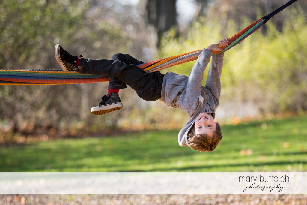 Boy hangs from a hammock in the backyard at Skaneateles