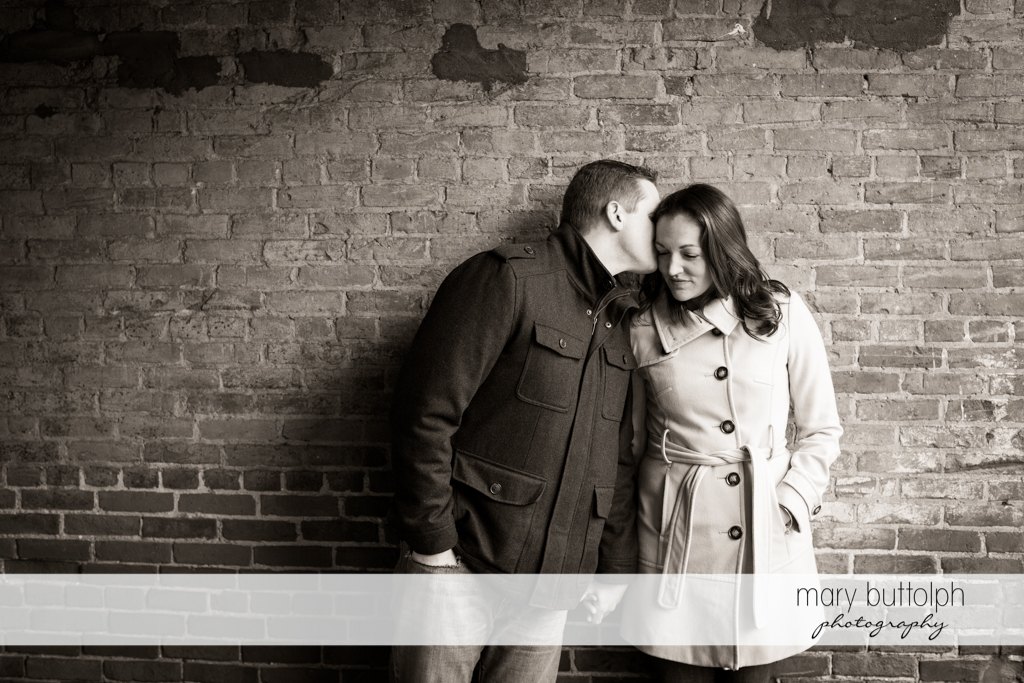 Man whispers to woman in front of a brick wall at Skaneateles Engagement