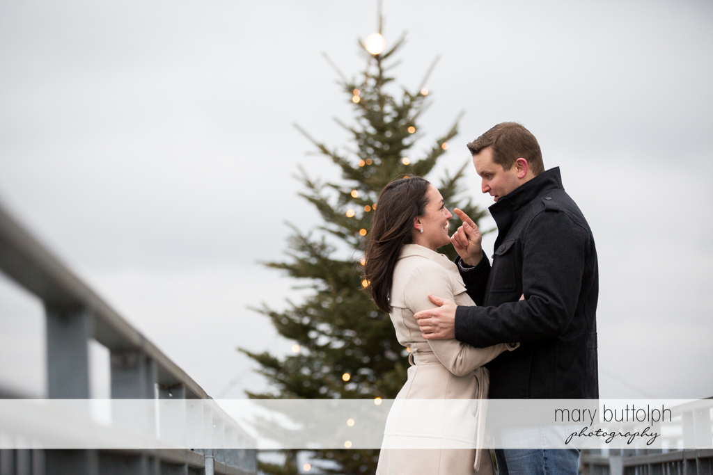 Couple stand in front of a Christmas tree at Skaneateles Engagement