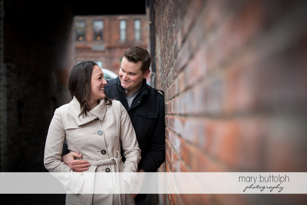 Couple pause by a brick wall at Skaneateles Engagement