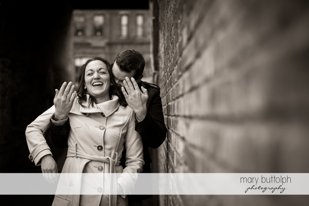 Couple clown around n front of a brick wall at Skaneateles Engagement
