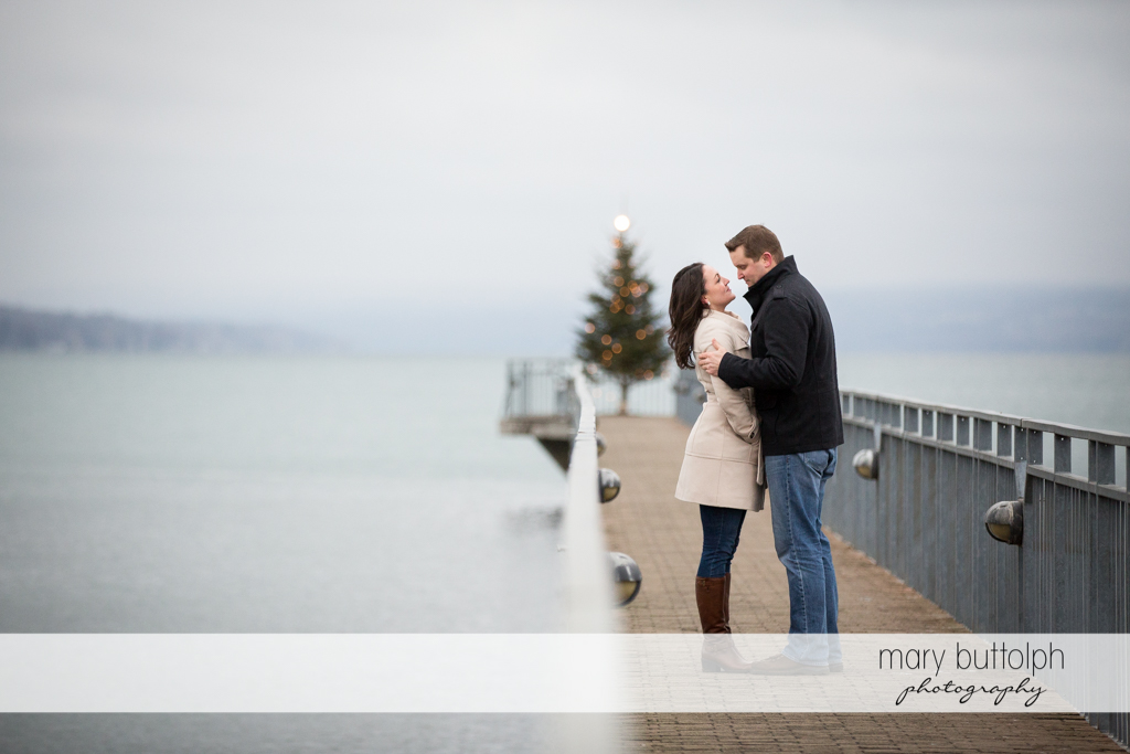 Couple stop by the lake with a Christmas tree in the background at Skaneateles Engagement