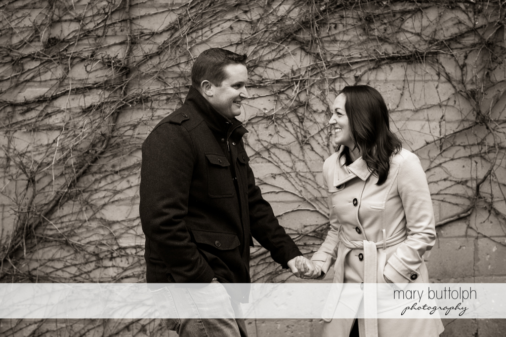 Couple hold hands by a stone wall at Skaneateles Engagement