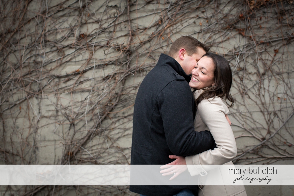 Couple embrace in front of a wall at Skaneateles Engagement