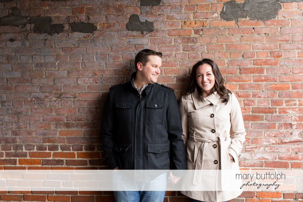 Couple stand against a brick wall at Skaneateles Engagement