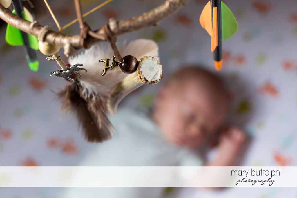 Crib toys hang over baby at Skaneateles Newborn